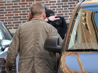 Ein mit einer schwarzen Jacke verdeckter Mann (M) wird von Polizeibeamten vom Amtsgericht Emden in einen Polizeibus geleitet. Foto: Michael Bahlo