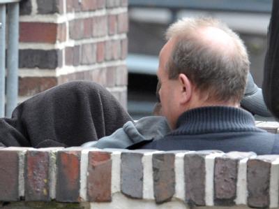 Ein mit einer schwarzen Jacke verdeckter Mann (l) wird von Polizeibeamten verdeckt aus dem Amtsgericht Emden geleitet. Foto: Carmen Jaspersen
