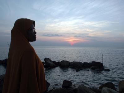 Eine Frau beobachtet den Meeresspiegel an der Küste von Pusong in Ace in Indonesien. Foto: Hotli Simanjuntak