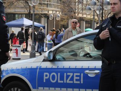 Polizeibeamte beobachten in Hannover das kostenlose Verteilen von Koran-Exemplaren an Passanten. Foto: Julian Stratenschulte