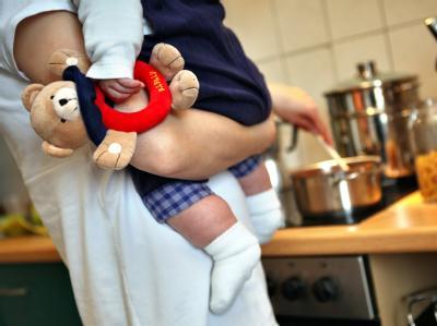 Betreuung zuhause: Eine Mutter kocht und hält dabei ihr Kleinkind auf dem Arm. Foto: Jan Woitas