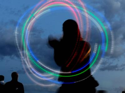 Ein Jongleur zaubert im Berliner Mauerpark Leuchtkreise. Foto: Maurizio Gambarini