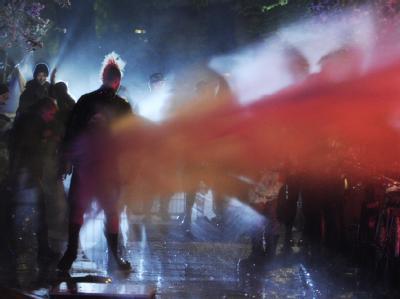 Demonstranten im Hamburger Schanzenviertel im Strahl eines Wasserwerfers. Foto: Angelika Warmuth