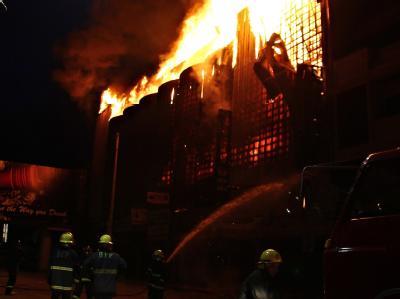 Feuerwehrleute während der Löscharbeiten: Drei Menschen haben sich mit einem Sprung aus dem Fenster retten können. Foto: STR