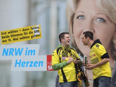 Zwei Fans von Borussia Dortmund in Dortmund vor einem Wahlplakat der alten und neuen Ministerpräsidentin Hannelore Kraft. Foto: Fabian Stratenschulte