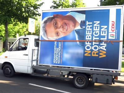 Ein Wahlplakat mit CDU-Spitzenkandidat Norbert Röttgen wird in Düsseldorf weggefahren. Foto: Martin Gerten