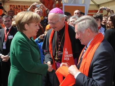 Alois Glück (r), Präsident des Zentralkomitees der deutschen Katholiken, und Erzbischof Robert Zollitsch (M), begrüßen Angela Merkel (CDU) zum 98. Katholikentag. Foto: Uli Deck