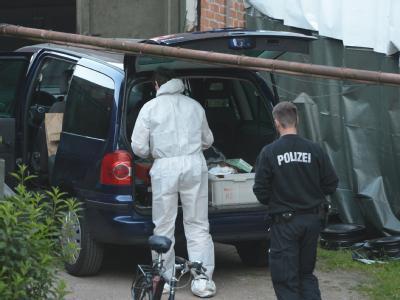 Ermittler der Spurensicherung der Polizei durchsuchen in Kiel das Gelände einer Kfz-Werkstatt. Foto: Marcus Brandt
