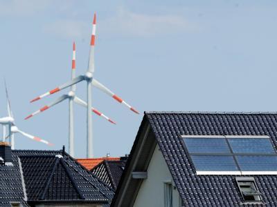 Windräder hinter Einfamilienhäusern mit Solarzellen am Stadtrand von Salzgitter. Foto: Julian Stratenschulte/Archiv