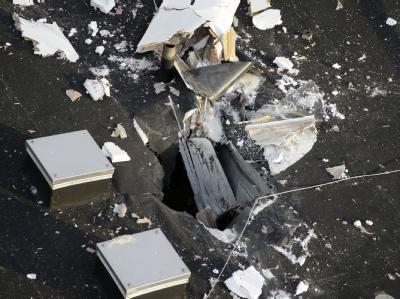 Stelle des Absturzes: Der Motorsegler durchbricht das Dach des Schulzentrums. Von dem toten Piloten werden nur noch Überreste geborgen. Foto: Markus Proßwitz