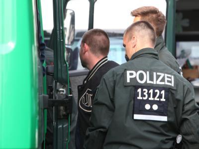 Ein mutmaßliches Mitglied einer Rockerbande wird in Hennigsdorf zur Feststellung der Personalien in ein Polizeifahrzeug geführt. Foto: Nestor Bachmann