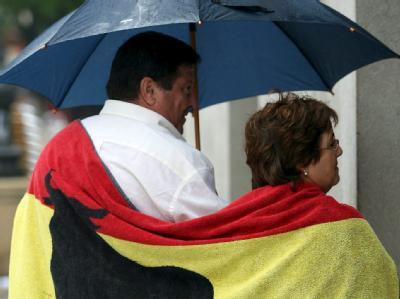 Ein Pärchen mit einem Handtuch in den spanischen Landesfarben schützt sich in Cadiz (Spanien) mit einem Schirm vor dem Regen. Foto: Jorge Zapata/Archiv