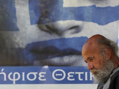Ein Obdachloser vor einem Wahlplakat in der Athener Innenstadt. Foto: Orestis Panagiotou