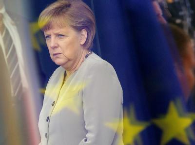 Bundeskanzlerin Merkel im Foyer des Bundeskanzleramtes in Berlin: Das Foto wurde durch die Scheiben des Kanzleramtes aufgenommen, in denen sich die Flagge der EU spiegelt. Foto: Wolfgang Kumm