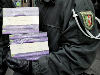 Polizeibeamte tragen Schriften aus der «Millatu Ibrahim Moschee» in Solingen. Foto: Henning Kaiser