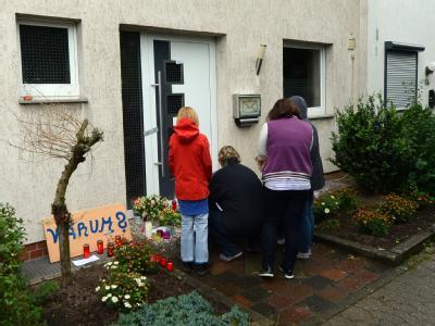 Nachbarn legen Blumen vor dem Haus in Ilsede nieder, in dem ein Vater vermutlich seine vier Kinder im Schlaf tötete. Foto: Peter Steffen