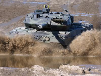 Ein Kampfpanzer vom Typ Leopard 2 fährt auf dem Truppenübungsplatz Munster durch ein Flussbett. Foto: Bundeswehr/Mediendatenbank/Winkler