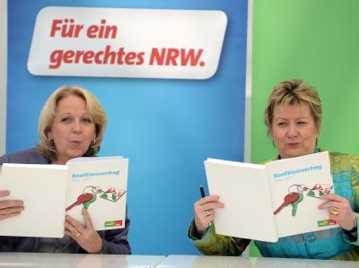 Koalitionsvertrag unterzeichnet: NRW-Ministerpräsidentin Kraft (SPD,l) und Schulministerin Sylvia Löhrmann (Grüne) pusten die Tinte trocken. Foto: Federico Gambarini