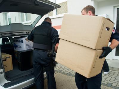 Polizeibeamte während einer Razzia bei Rechtsextremisten im brandenburgischen Lübbenau. Foto: Patrick Pleul