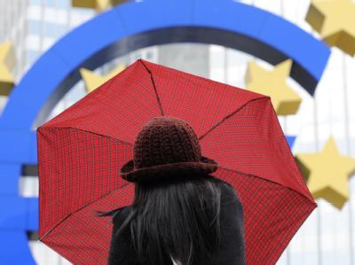 Eine Frau spannt bei regnerischem Wetter vor der Euro-Skulptur in Frankfurt am Main ihren Regenschirm auf. Foto: Arne Dedert/Archiv