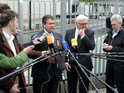 Der Fraktionschef der SPD, Frank-Walter Steinmeier (Mitte r) und der Vorsitzende der Partei, Sigmar Gabriel (Mitte l), informieren vor dem Kanzleramt in Berlin wartende Journalisten. Foto: Wolfgang Kumm
