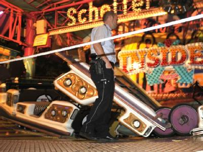 Ein Polizist sichert die Unfallstelle auf der Kirmes in Gevelsberg: Aus noch ungeklärter Ursache hatte sich eine Gondel von einem Fahrgeschäft auf gelöst. Sieben Menschen wurden verletzt. Foto: Holger Battefeld