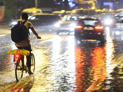 Radeln im Regen: Hannover steht unter Wasser. Foto: Julian Stratenschulte