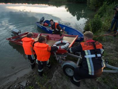 Einsatzkräfte schieben ein Boot in den Mittleren Klausensee bei Schwandorf (Oberpfalz) um nach einem Krokodil zu suchen. Foto: Armin Weigel