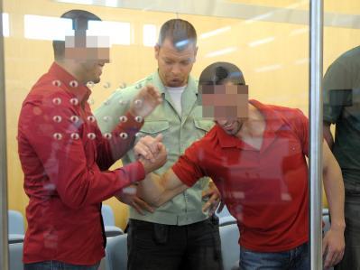 Abdeladim El-K. (r) und Amid C. treffen sich zu Prozessbeginn im Gerichtssaal. Foto: Federico Gambarini