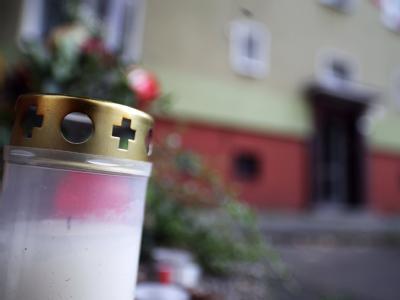 Eine Kerze, die an die drei getöteten Kinder erinnert, steht vor der ausgebrannten Wohnung in Dortmund. Foto: Daniel Naupold