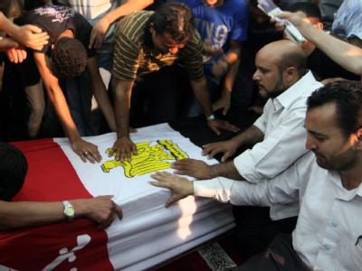 Verwandte und Freunde trauern an dem Sarg eines der 16 Getöteten. Foto: Khaled  Elfiqi