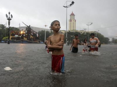 Kinder waten bei strömendem Regen durch die überflutete Straße. Foto: Francis R. Malasig