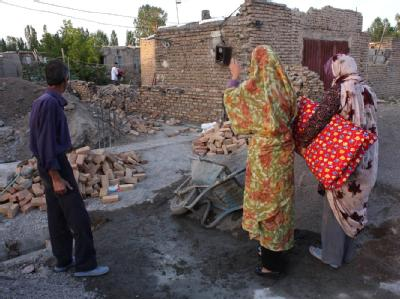 Eine Familie steht vor den Trümmern ihres Hauses. Foto: Stringer