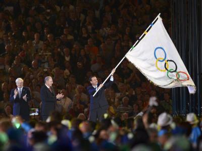 Eduardo Paes, Bürgermeister von Rio de Janeiro, schwenkt die olympische Fahne. Foto: Christophe Karaba