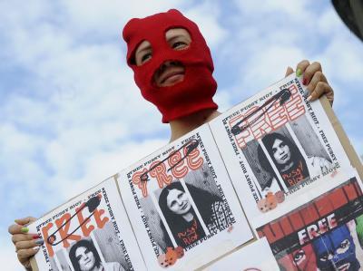 Eine Demonstrantin in Prag fordert die Freilassung der russischen Musikerinnen. Foto: Filip Singer