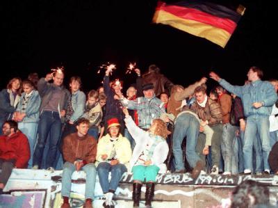Jubelnde Menschen freuen sich 1989 auf der Berliner Mauer über die Öffnung der deutsch-deutschen Grenzen.