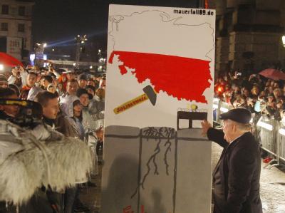 Der frühere polnische Staatspräsident Lech Walesa (r) bringt die symbolische Mauer aus Dominosteinen zum Einsturz.