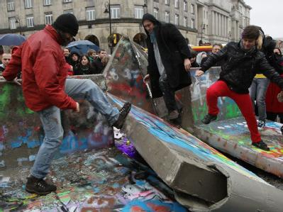 Teilnehmer eines Happenings in Warschau trampeln symbolisch die Mauer nieder.