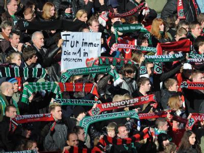 Fans halten ihre Fanschals während der Trauerfeier in Hannover hoch.