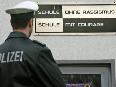 Ein Polizist steht vor der Heideschule in Bergkamen.
