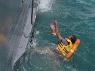 Die Besatzung eines Schiffes birgt eine überlebende Person aus dem Meer.