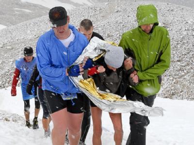 Wettkampfteilnehmer stützen am 13.07.2008 eine völlig erschöpfte und durchgefrorene Läuferin während eines Extrem-Berglaufs auf der Zugspitze.