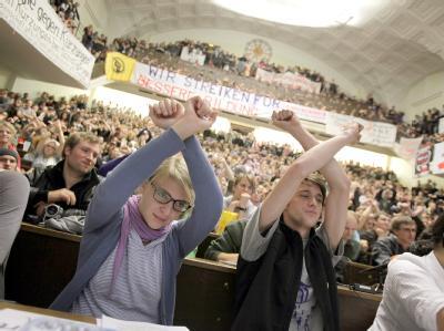 Studenten symbolisieren mit überkreuzten Armen im Audimax der Ludwig-Maximilians-Universität in München, dass sie nicht der Meinung des Redners sind.