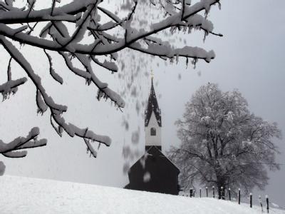 Blick auf die winterliche Landschaft rund um die Kirche von Bolsterlang in Bayern.