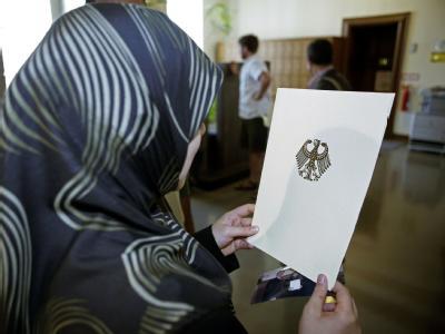 Eingebürgert: Eine Frau mit einer Einbürgerungsurkunde der Bundesrepublik Deutschland im Rathaus Berlin-Neukölln. (Archivfoto).