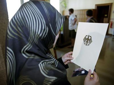Eingebürgert: Eine Frau mit einer Einbürgerungsurkunde der Bundesrepublik Deutschland im Rathaus Berlin-Neukölln (Archivfoto).