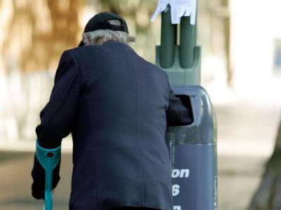 In einem Mülleimer in Berlin sucht ein alter Mann nach Verwertbarem.