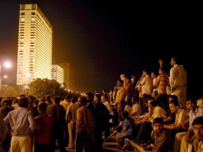 Menschen beobachten das Geisel-Drama im Luxushotel «Oberoi Trident» in Bombay (Foto vom 27.10.2008).