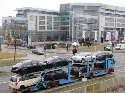 Ein mit Neuwagen beladener Autotransporter fährt  am Opel-Stammsitz in Rüsselsheim vorbei.