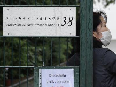 Eine Frau mit Mundschutz am Tor der Schule in Düsseldorf.